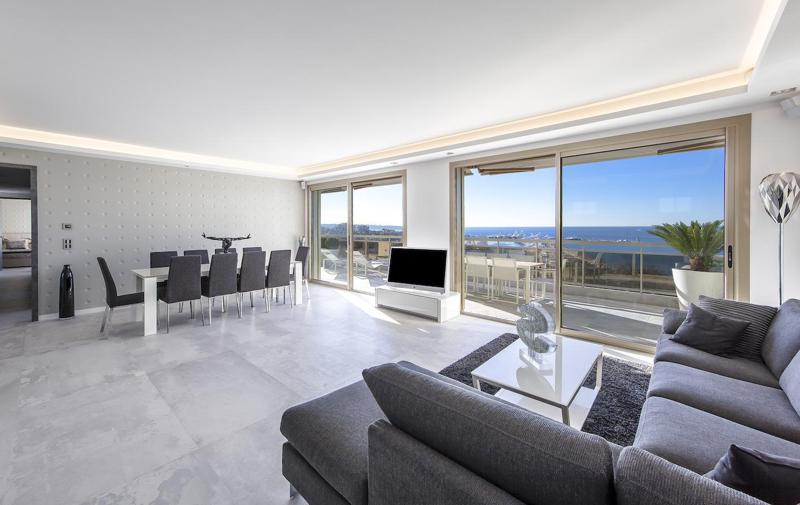 Living room with white interiors, dining area, dark grey couches and chairs with a sea view in a Cannes group accommodation