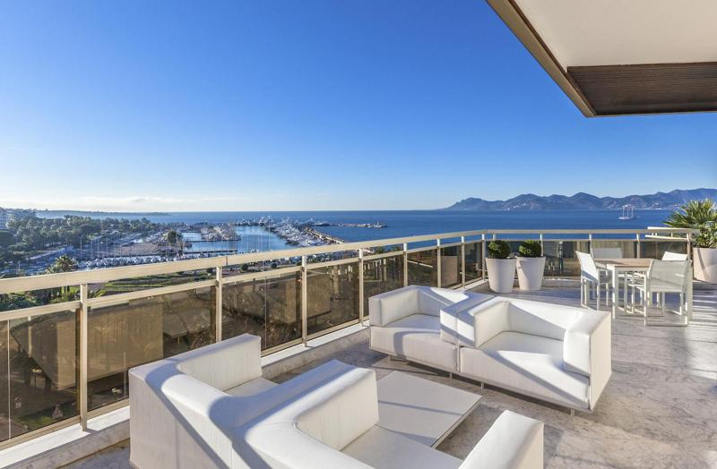 Outdoor terrace seating area with white couches and sea and port view in a Cannes group penthouse