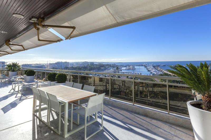 Cannes city and sea views from the terrace with lounge chairs and couches for sunbathing of a group rental penthouse