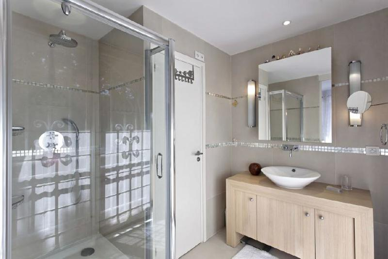 Bathroom with glass enclosed standing shower and a wooden cabinet underneath the sink