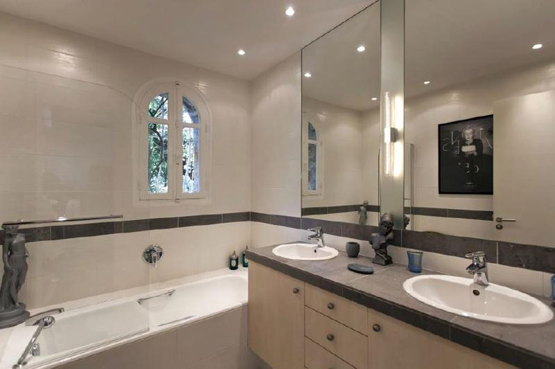 Bathroom with a bathtub, artistic sculptures, dual sink and a window in Cannes