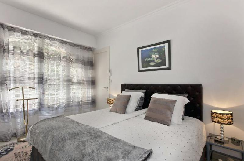 Double bedroom with window curtains, white sheet and grey blanket