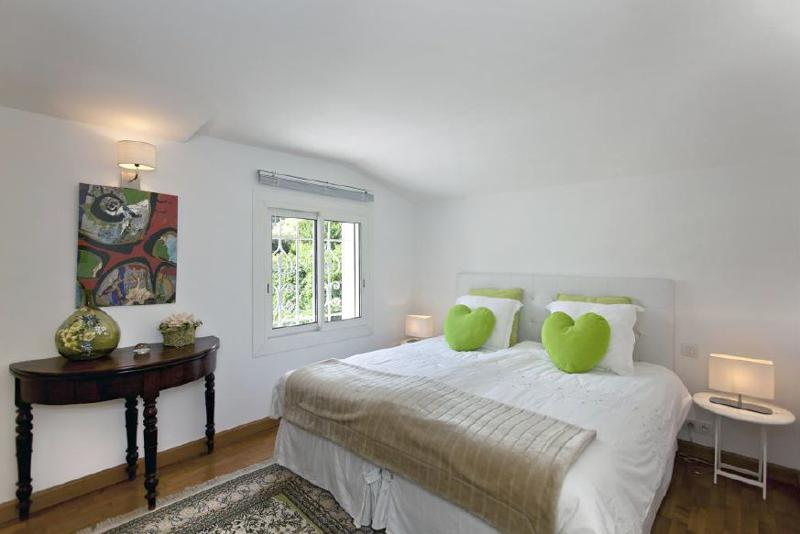 Double bedroom with green heart-shaped cushions and a window overlooking the garden in Cannes