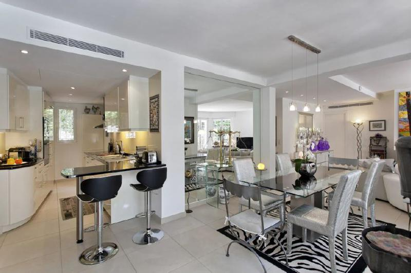 Open kitchen with black coloured bar stools, next to the living room with dining table in a north Cannes group rental villa