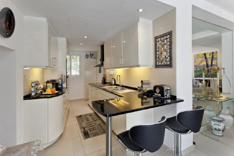 Open kitchen with bar stools, coffee maker, toaster, microwave, oven and induction stove next to the living room in Cannes