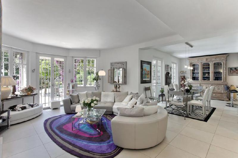 Living room with leather couches, cushions and open dining area in a Cannes luxury villa