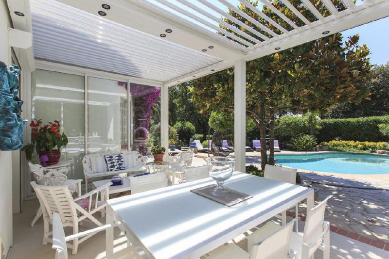 Outdoor dining and relaxing area next to the swimming pool in a rental villa in Californie Pézou