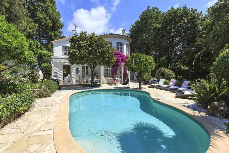 Swimming pool surrounded by sunbathing chairs and overlooking the Cannes private rental villa