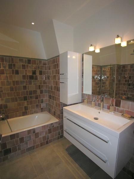 Bathtub, white sink, a mirror and a storage cabinet in the bathroom