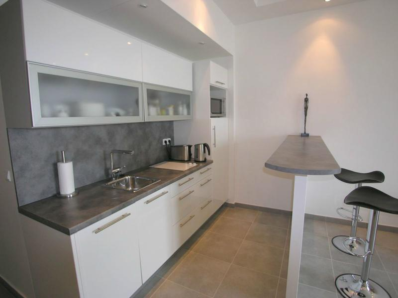 Open kitchen with coffee maker, toaster, microwave, refrigerator and bar stools