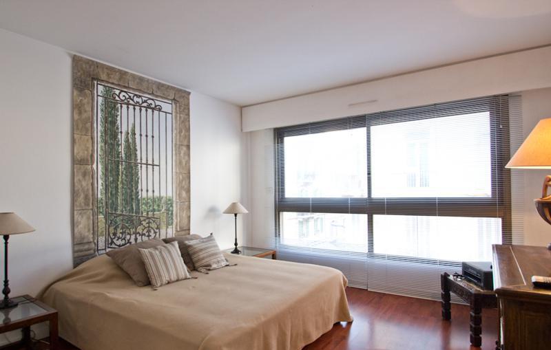 Double bedroom with a blanket and cushions, painting and large windows with blinds in a Central Cannes apartment