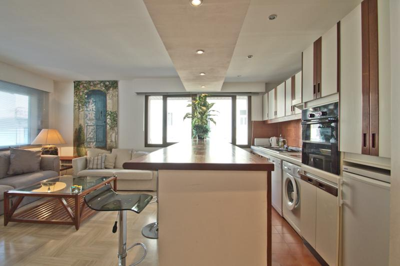 Open kitchen in a living room with natural light, cream and brown countertop and shelves in a Cannes group accommodation