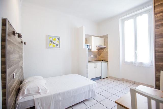 Open kitchen, double bed and desk in a Cannes studio accommodation near Palais des Festivals