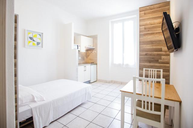 Double bedroom, flat screen tv, open kitchen and a table with 2 chairs in a Cannes studio rental apartment