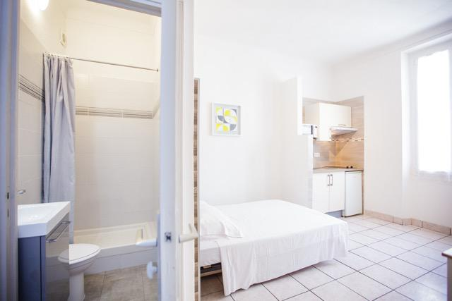 Double bed, open kitchen and attached bathroom in a Cannes studio apartment building close to the convention centre