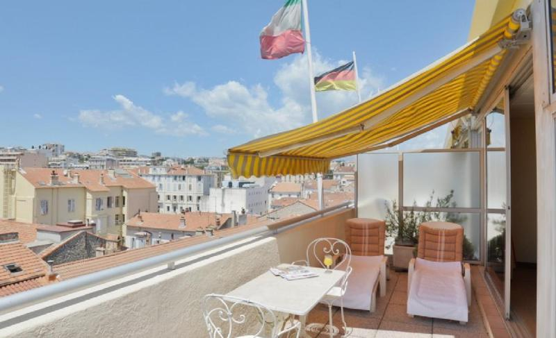 Terrace with lounge chairs for sunbathing and shade in a Cannes event accommodation