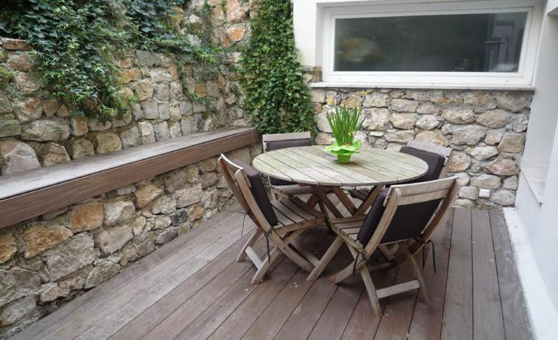 Backyard with round wooden table and chairs in a Cannes rental townhouse