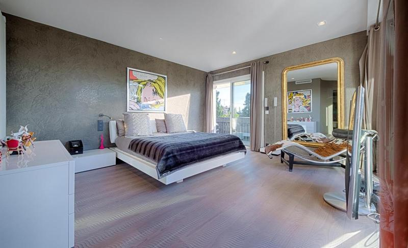 Double bedroom with a large mirror, recliner chair, beige floor and walls and access to a terrace in Cannes group villa