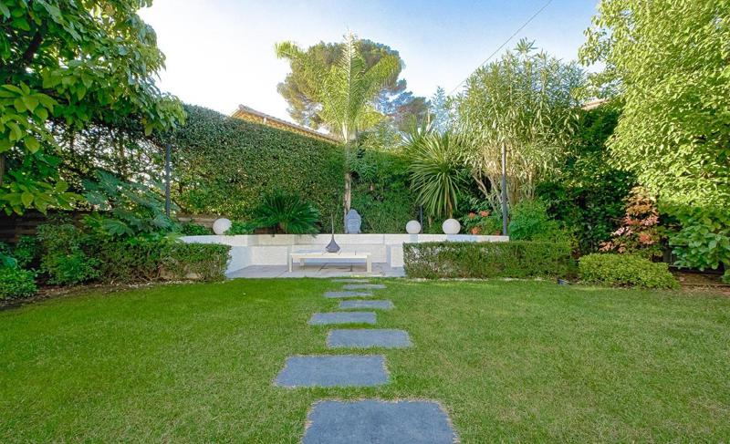 A garden with a stone path leading to outdoor sitting in a Cannes party villa