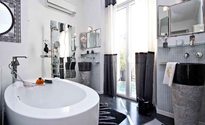 White soaking bathtub in the centre of a stylish black floored bathroom with door to terrace in Cannes rental apartment