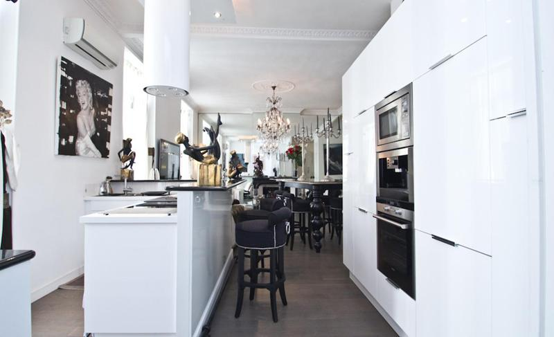 White and black themed living room with open kitchen, wall painting and stools in Cannes rental apartment
