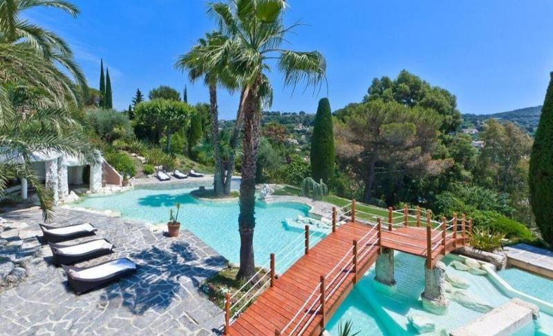 Lounge chairs by the swimming pool with a small wooden bridge in the mountains in a Cannes group party villa