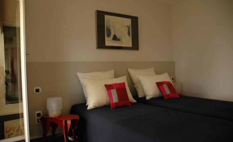 2 single beds with black bedsheets, white pillows and a closet with a mirror in a Cannes bedroom