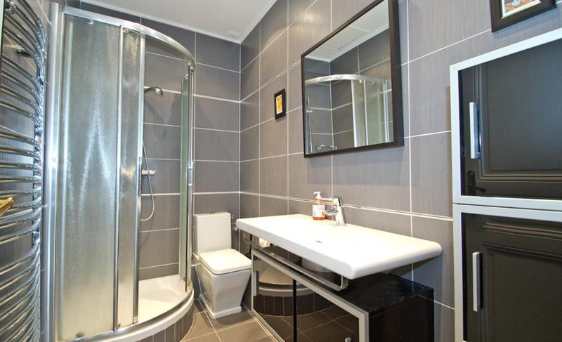Grey tiles in the bathroom with standing shower, a toilet, a sink, a mirror and storage space