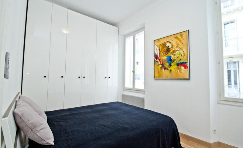 Double bedroom with a blue blanket, beige coloured pillows, a painting on the wall, a spacious wardrobe and Cannes view