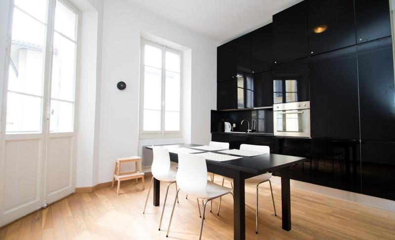 Black polished cabinets and open kitchen in Cannes with a dining table in a smart Cannes rental accommodation for events