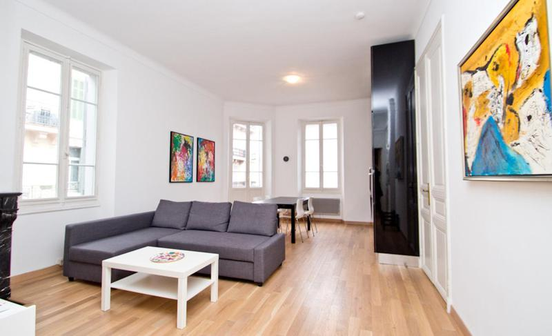 Bright living room with grey couch set and a table for meetings in a 2 bedroom Cannes group rental apartment in Le Suquet