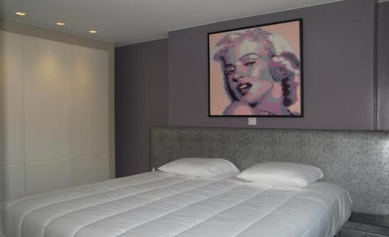 Double bed with white sheets and pillows and a painting on the wall behind