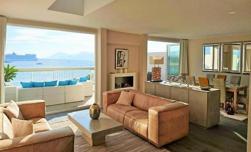 Sand coloured couch sets in the living room overlooking the terrace lounge in a Cannes sea facing group penthouse for rent