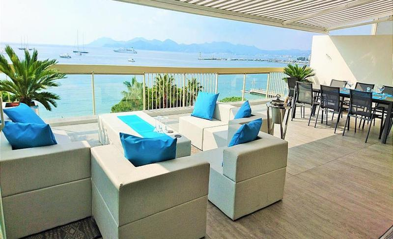 Sea facing terrace with couches and 8 person table for meetings in a Cannes party penthouse near to Palais des Festivals