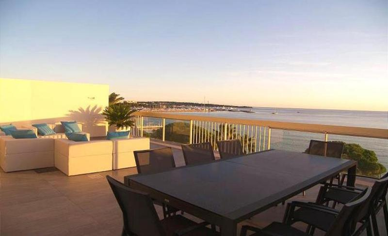 Sea facing terrace lounge with couches and 8 person dining table in a Cannes rental penthouse for groups on the Croisette