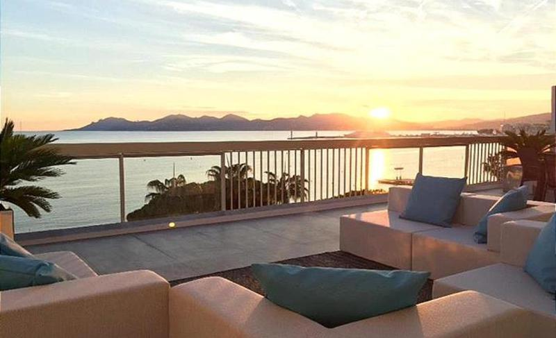 Sunset and sea view from the terrace of a Cannes group accommodation with peach coloured couch set and blue cushions