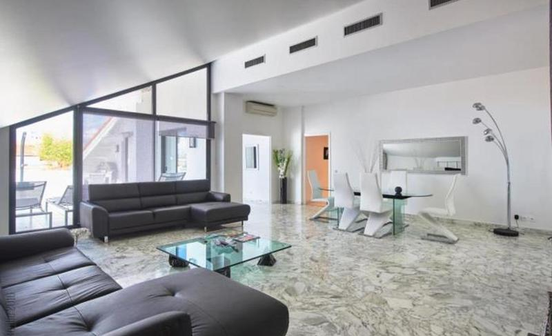 Living room of a Cannes rental penthouse with black couch sets and a glass dining table with white chairs