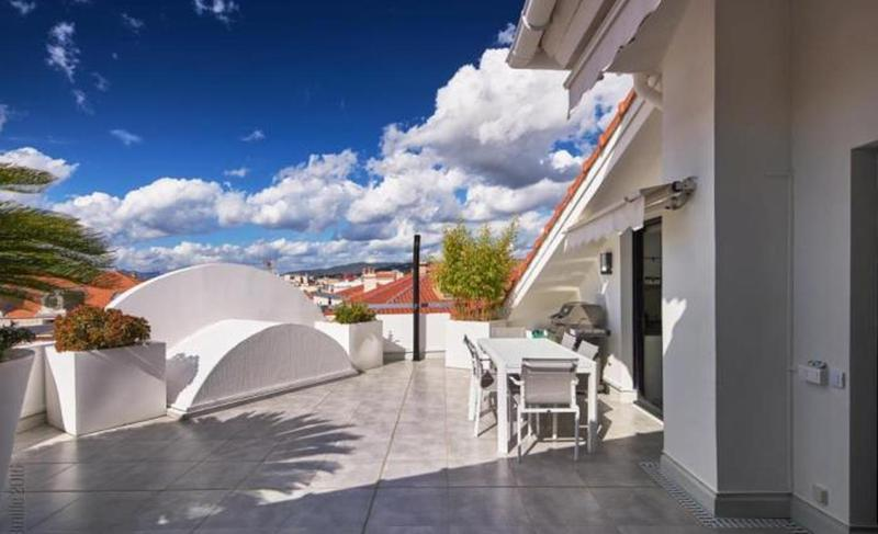 Sunny penthouse terrace with dining table and view of the city in a Cannes event accommodation near to Palais des Festivals