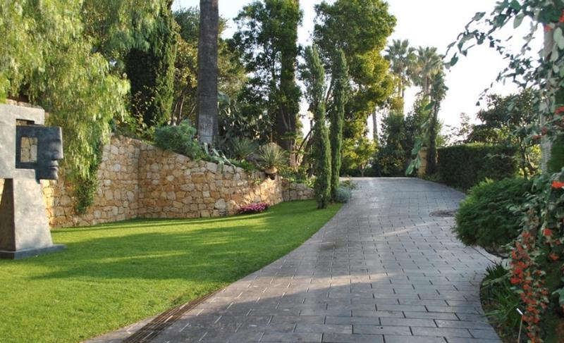Driveway surrounded by trees inside a Cannes group villa with stone face sculpture