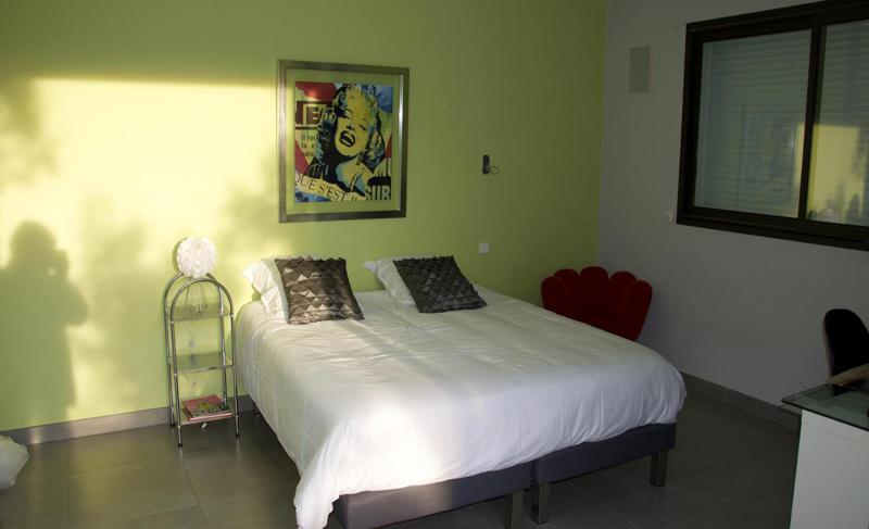 A painting of Marilyn Monroe on a green wall in the double bedroom with white covers in Cannes