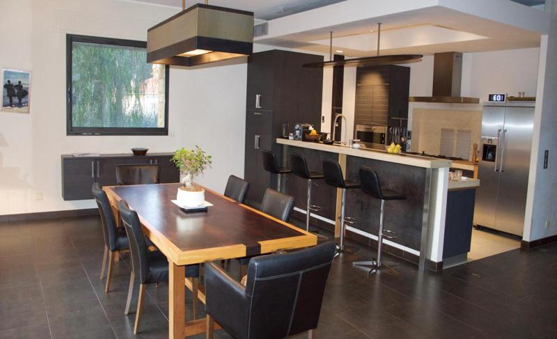 Open kitchen with bar stools and a dining area with table and chairs in a Cannes villa