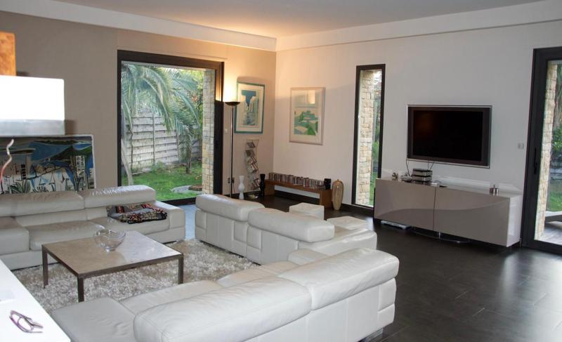 White leather couch set and 2 sofas facing the tv in the living room of a Cannes rental villa with art and paintings