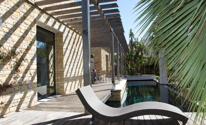 Yellowstone walls and sunbathing lounge chairs next to a swimming pool in a Cannes rental villa