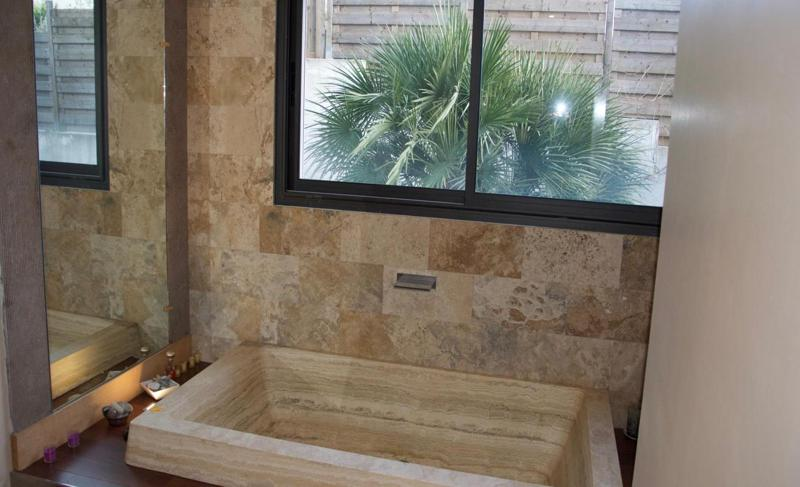A polished stone sink with a window above it looking at a plant outside