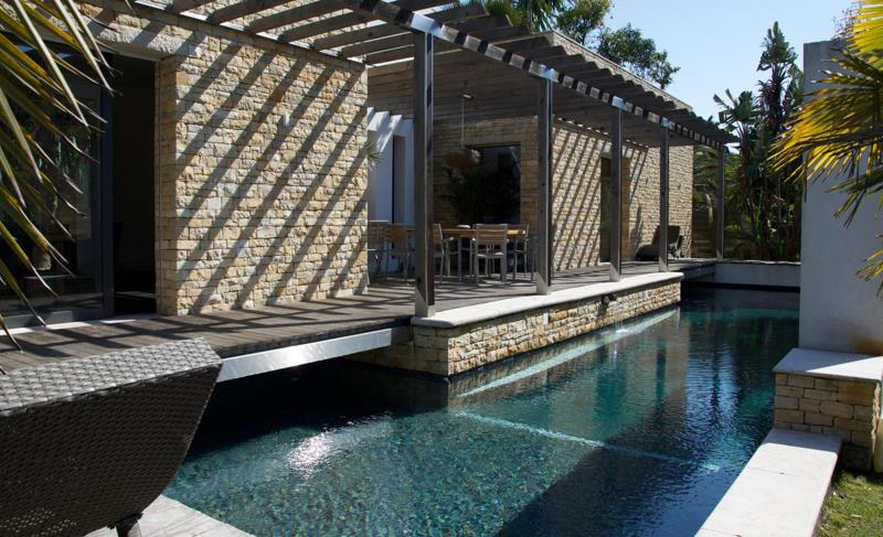 Lounges chairs and a dining table next to the swimming pool in a rental Cannes Lions group villa with Yellowstone walls