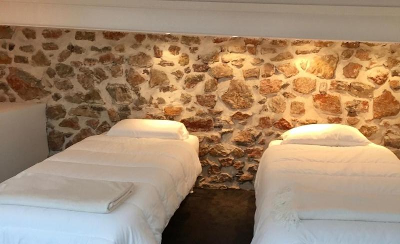 2 single beds with neatly arranged bed linen in a stone-walled bedroom
