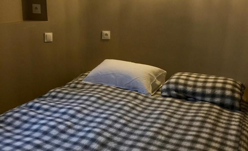 Double bed with checkered blanket in a 6 bedroom villa in Cannes