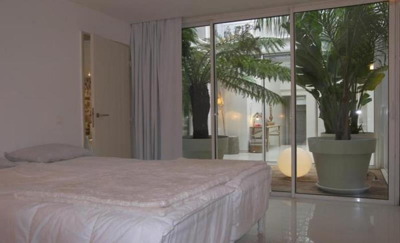 Spacious bedroom with a glass wall providing a view of beautiful plants in the inner patio of a group event villa in Cannes