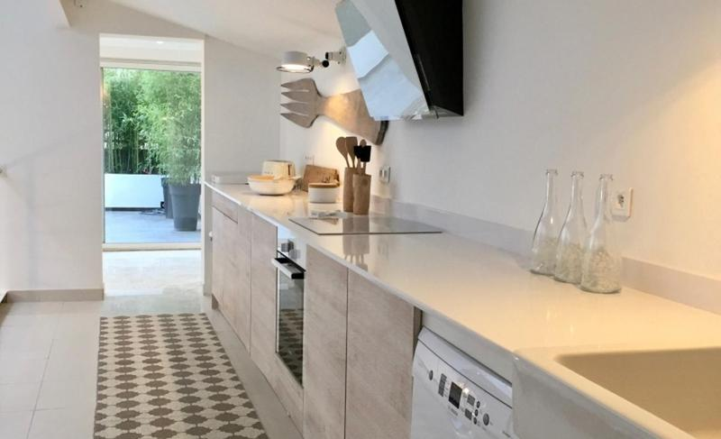 Modern white marble kitchen leading to an outdoor deck in a Cannes villa.