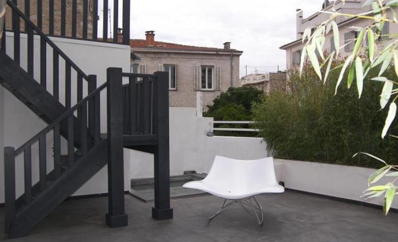 Black staircase on a terrace of group villa with views of surrounding buildings in Cannes